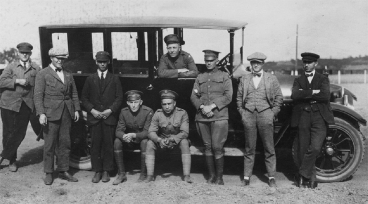 "Clive Mason posed with a group of his buddies and co-workers, fourth from the right sitting on the car's running board. Some of the men who are not in uniform may be either civilian CID agents or German employees of the AFG. With each reduction in assigned ""strength,"" the AFG hired more local citizens, mainly German Army veterans. They worked as mechanics, quartermasters, and security guards, creating perhaps one of the great ironies of the American occupation: Armed German ex-soldiers guarding the facilities in which the Americans were working and living."