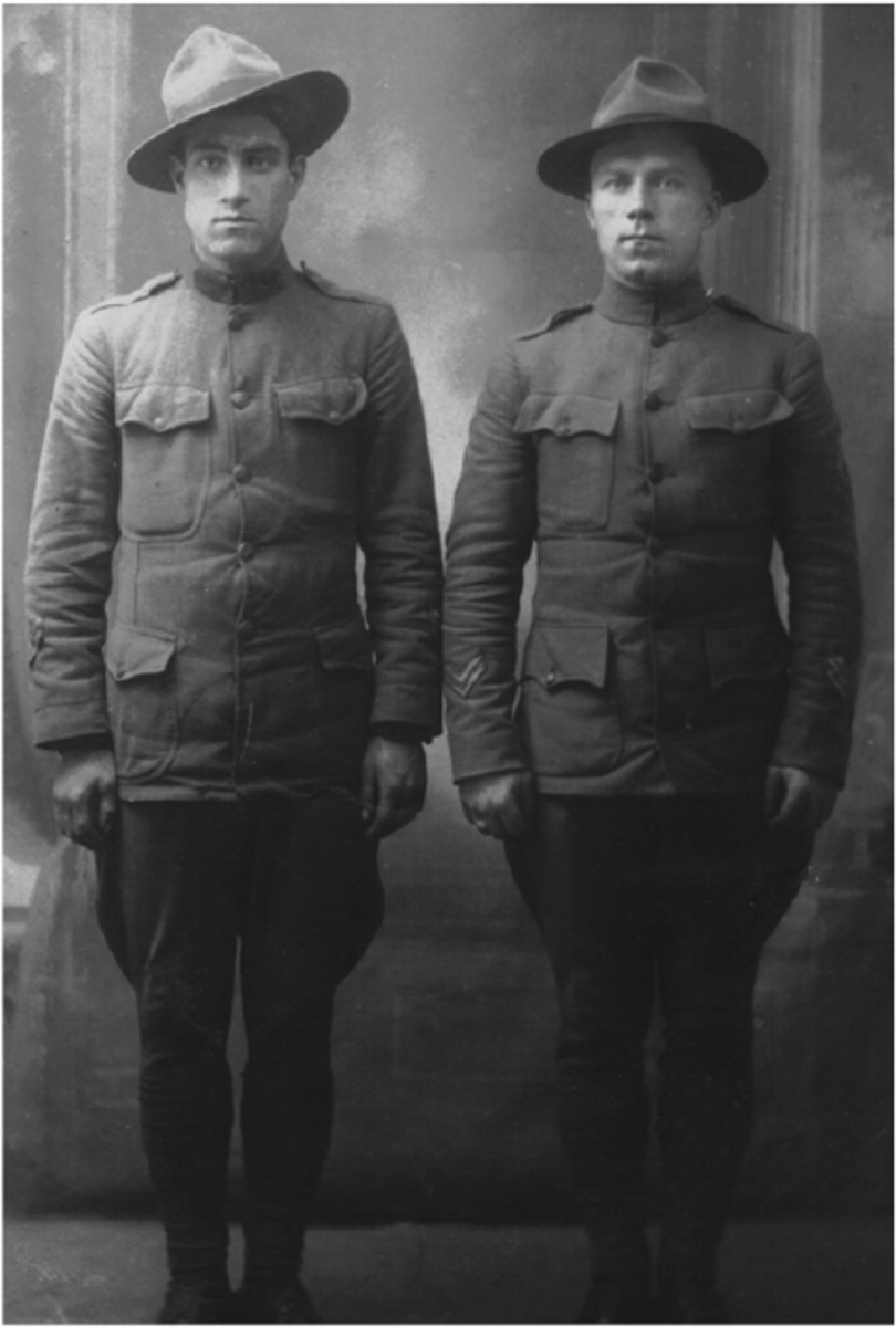 "Among Clive Mason's personal papers was this badly damaged photo. He marked it as being two of his good pals. Though it may not have been taken in Coblenz, this photo is relevant for the subject matter. The soldier on the left appears to have the long felt collar ""rectangles"" that were favored by military police units as backing for their disks. Equally importantly, both of these soldier show two wound stripes each on their right sleeves and three overseas stripes on their right, and while their uniform coats appear to be too small and are stretching at the buttons, they both appear to be ""bon soldats."""
