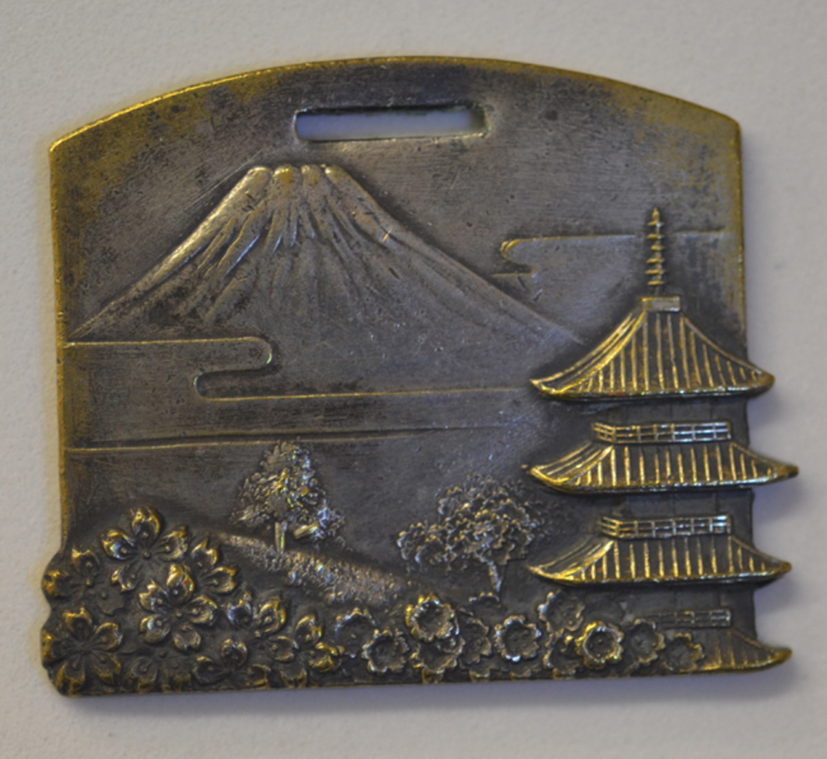One of the early Japanese Occupation souvenir medals is rectangular and depicts Mt. Fuji and cherry blossoms.