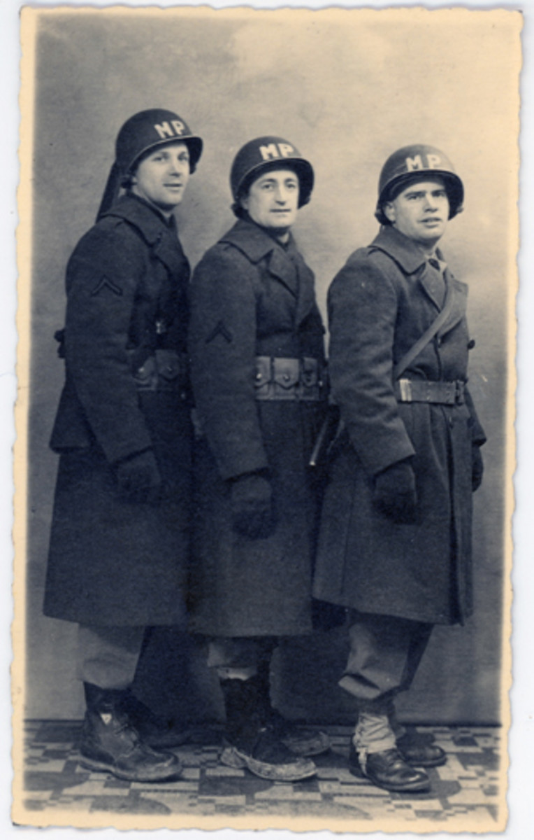 """Three MPs posed in a European studio, ca. 1945, wearing a variety of gear, including M1 helmets with painted """"MP"""" insignia."""