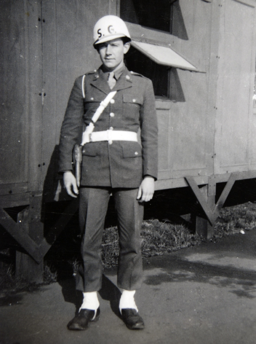 "Wearing a white-painted helmet liner with ""S.G."" on the front, this Army soldier, ca. 1943, is also wearing a white-painted Sam Browne belt and white leggings."