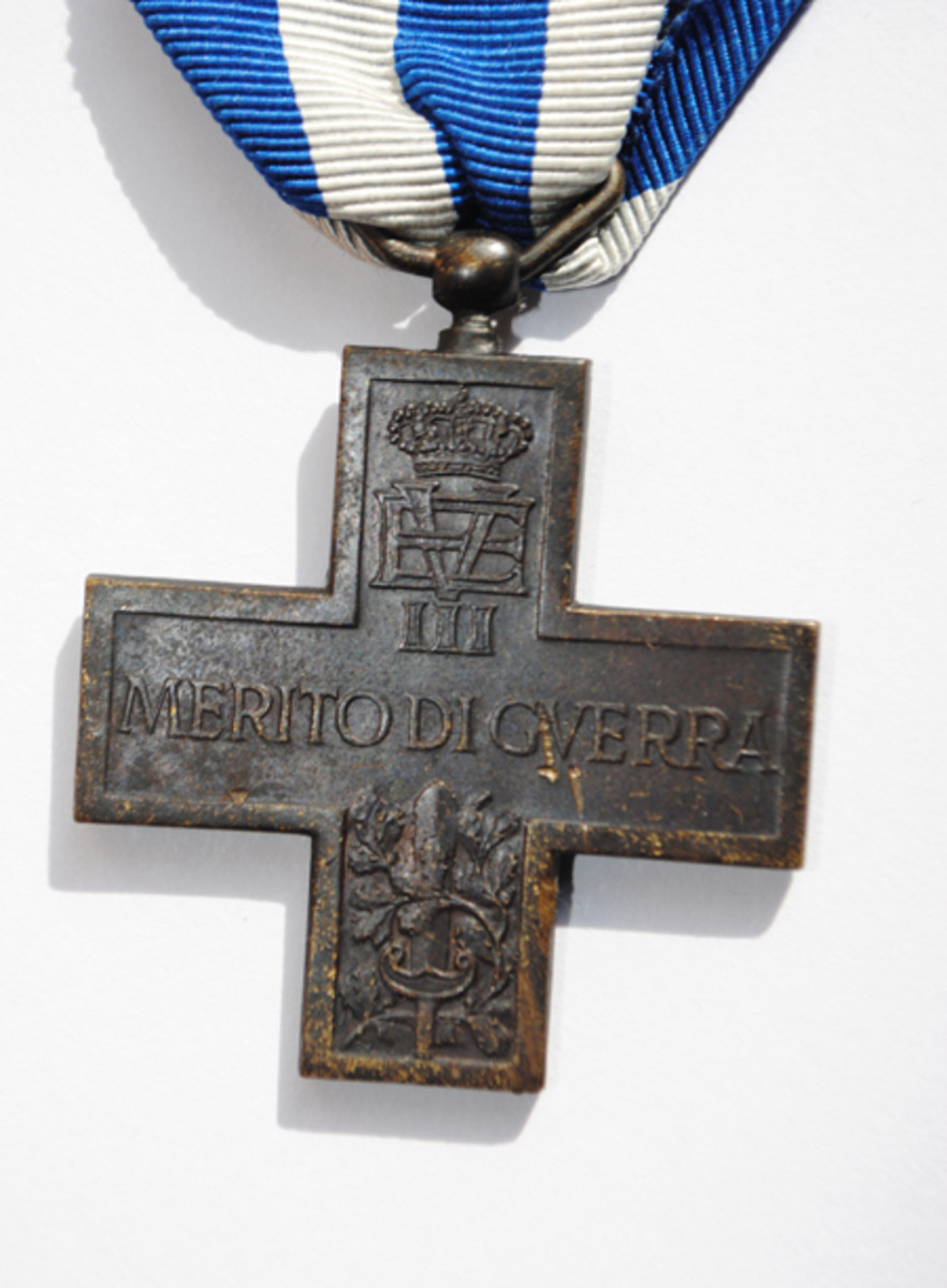 The reverse of the 'Royal' version of the Cross for War Merit, showing the cypher and crown of King Victor Emanuel III in the upper arm of the cross. This example has sustained some damage due to poor storage.