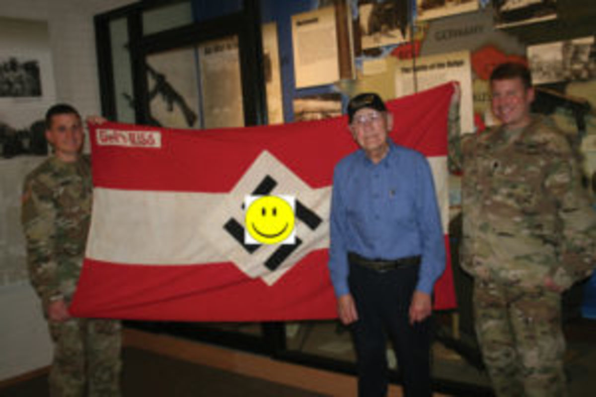 World War II Army veteran Charlie Brown of Olean, New York displays his captured Hitler Youth battle flag from his combat experience in Europe as part of the 258th Field Artillery Battalion with Lt. Col. Peter Mehling, right, and Capt. Steven Kerr, left, the current battalion commander and operations officer of the New York Army National Guard's 1st Battalion, 258th Field Artillery at the New York State Military Museum in Saratoga Springs, New York November 20, 2017. ( U.S. National Guard photo by Col. Richard Goldenberg.)