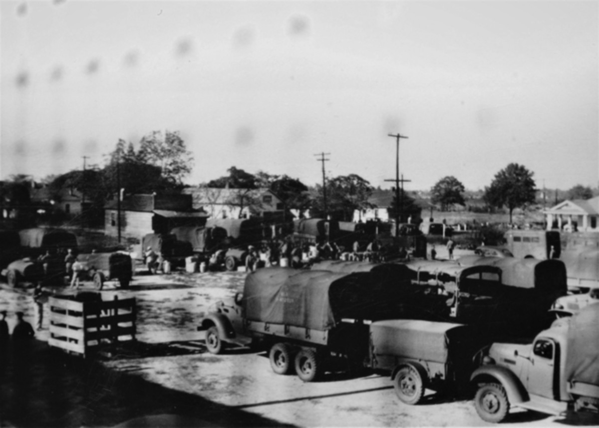 Convoy form-up during the 3rd Attack Group's participation in the Summer 1941 Maneuvers. This photo was taken through a fence and shows a variety of cargo trucks, trailers, and a crew bus.