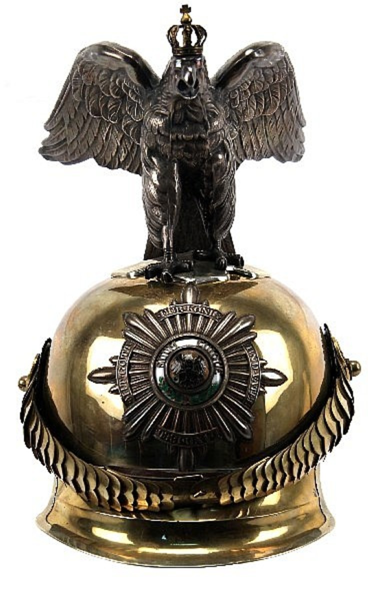 "Officer's helmet of the very small but elite ""Garde du Corps,"" in very good condition throughout. Personal bodyguards of the king of Prussia, and after 1871, the Kaiser. This helmet has the Tombak metallic body with large convex style gilt chin-scales secured to clover leaf rosettes; one with the colors of the German nation and the other the black and white Prussian colors. Excellent example of an Imperial relic. Included is a wooden box for storage and transportation of helmet (box not period). Estimated Price: $17,000-$18,000"