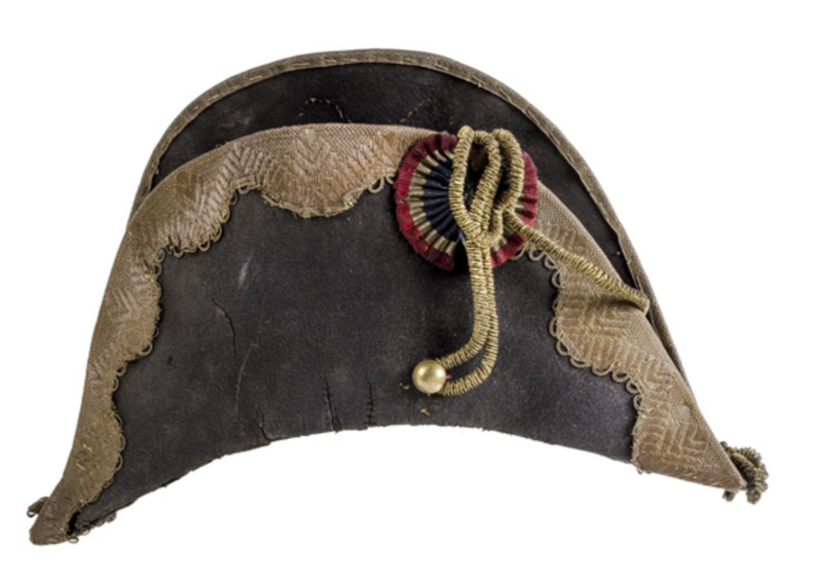 Napoleonic bicorne (or bicorn) with gold officer's litzen and French red, white and blue cockade. The bicorne (two-cornered/horned) is an archaic form of hat widely adopted in the 1790s ... (EST $2500-$3500)