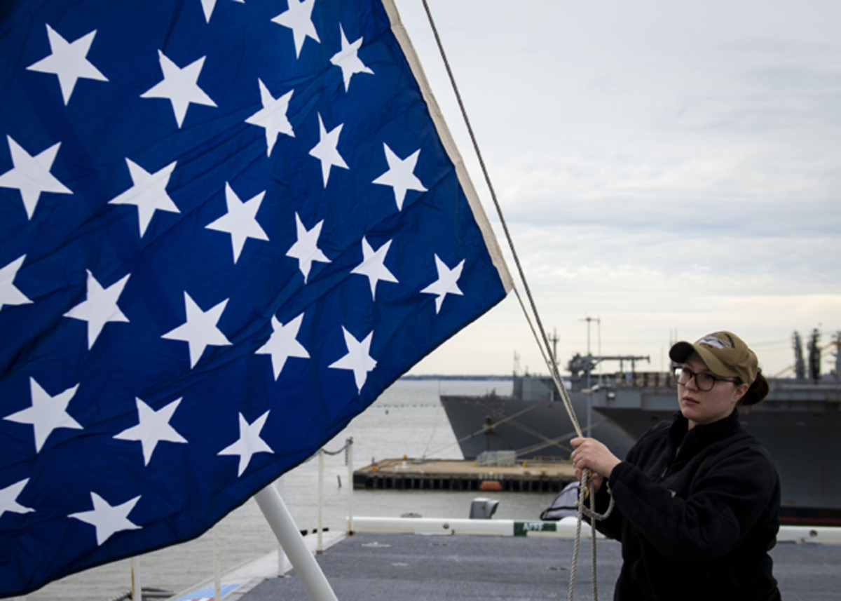 190219-N-QD512-0022NORFOLK (Feb. 19, 2019) Quartermaster 2nd Class Taylor Miller, from Kent, Ohio, unfurls the union jack on the jack staff of the aircraft carrier USS Dwight D. Eisenhower (CVN 69). Dwight D. Eisenhower is undergoing a planned incremental availability during the maintenance phase of the Optimized Fleet Response Plan. (U.S. Navy photo by Mass Communication Specialist 3rd Class Kaleb Sarten/Released)