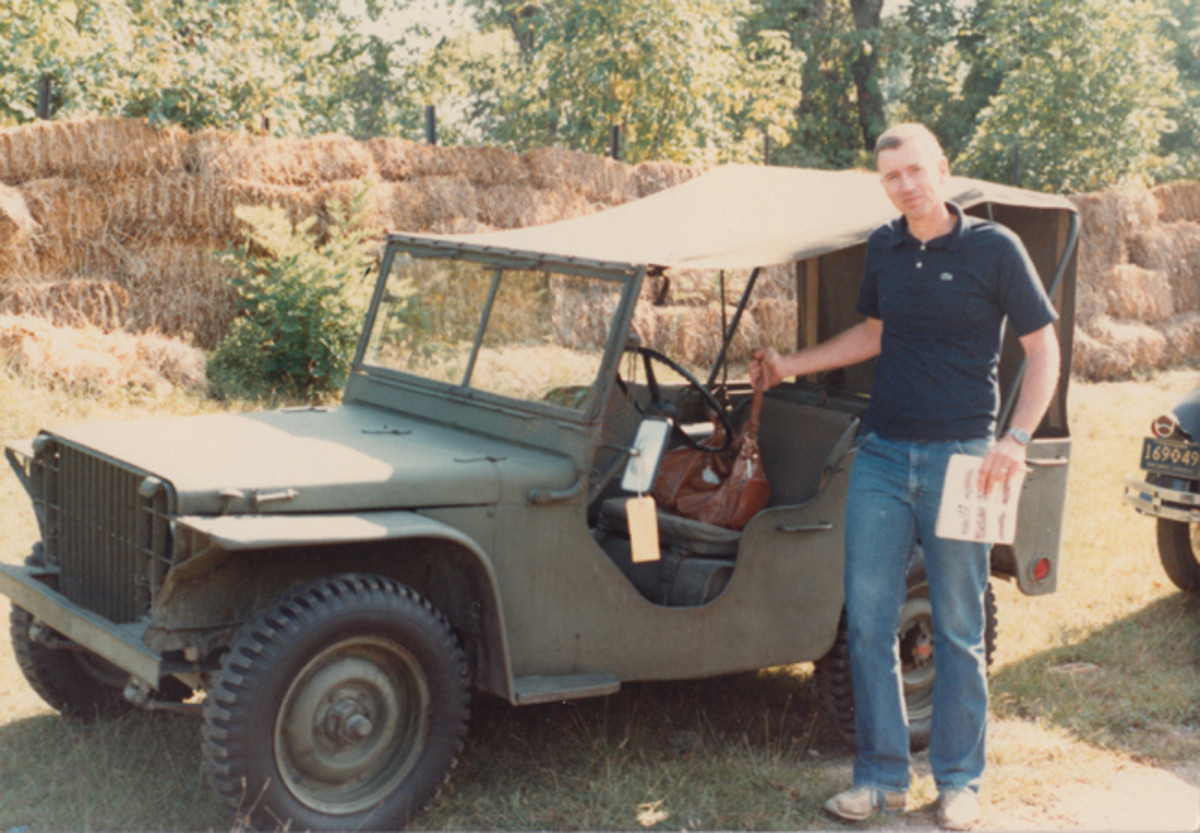 """Randall Withrow proudly stands next to the 1940 Ford Pilot Model GP-No. 1 (Pygmy) after purchasing the """"jeep"""" on 19 September 1982 at the Henry Ford Museum and Greenfield Village public auction in Dearborn, Mich. Note the auction catalog in hand and yellow hangtag on mirror."""