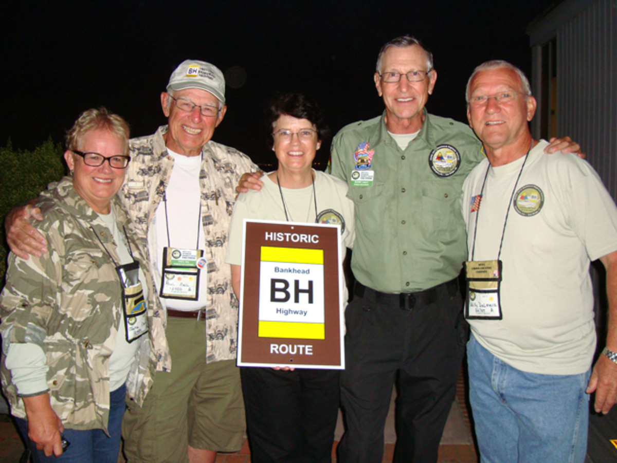 At the end of a successful convoy, it's time to tell stories and reminisce while seeing all of the happy smiles. Jeep March Unit Leaders Jackie and Paul Neil, Support Unit Leaders Traci and Randy Parent, and photographer Willy Delmeire show off an official Bankhead Highway sign. Willy Delmeier