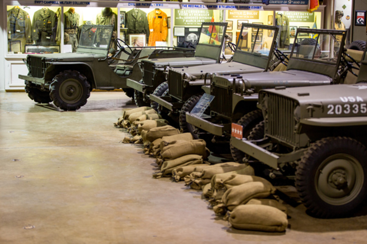 """The 1940 Ford Pilot Model GP-No. 1 Pygmy is placed at the head of a row of rare and early """"jeeps"""" at the U.S. Veterans Memorial Museum, illustrating the vehicle's lineage. From left to right: 1941 Ford GP (serial no. 9911), 1941 Bantam BRC (serial no: 1208), 1941 Willys MA (serial no. 85504), and 1941 Willys MB """"Slat Grill"""" (serial no. 102157 and serial no. 105312)."""