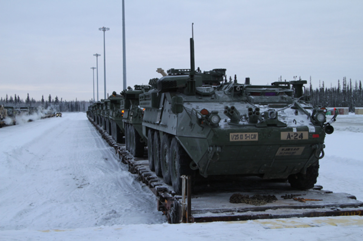 Strykers and other vehicles wait to be driven off train cars at Fort Wainwright, Alaska, Dec. 9, 2015. The return of the vehicles signals the end of the Pacific Pathways mission in Japan and Korea.
