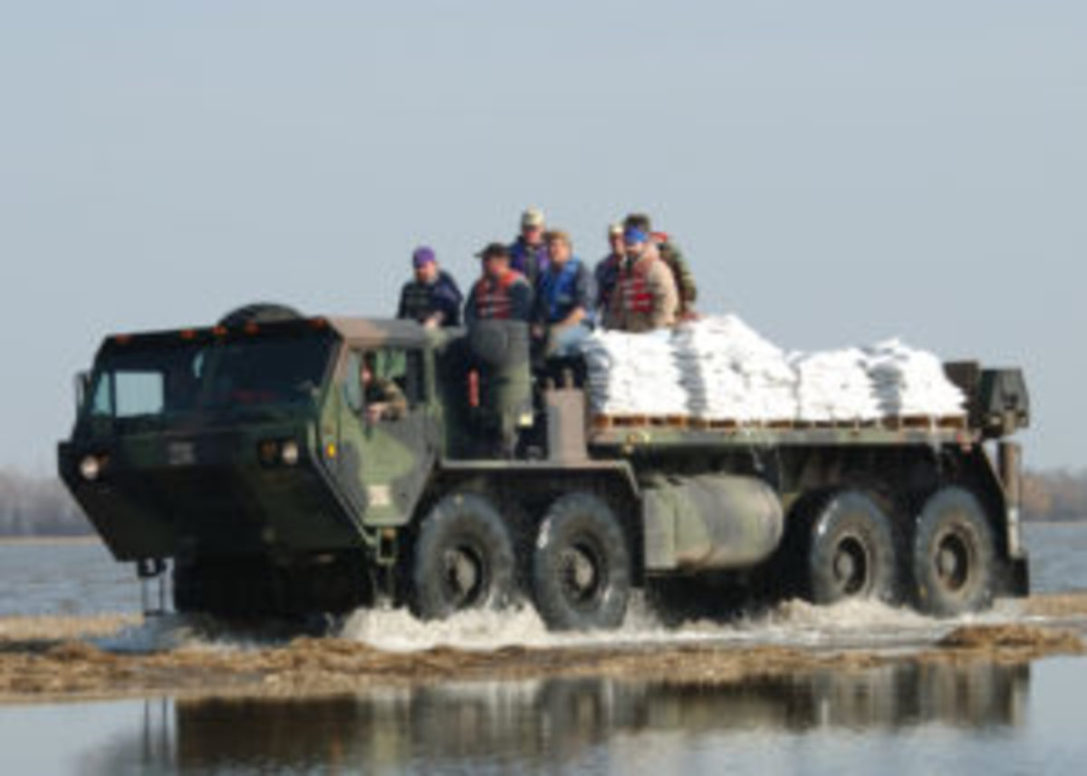 Minnesota National Guard and volunteers used high-wheel HEMTTs to carry sandbags and supplies during a 2006 flood.