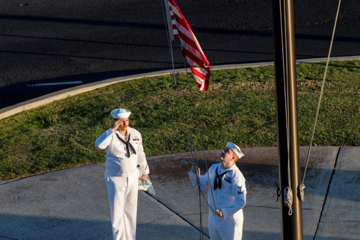 """Navy Petty Officer 2nd Class Gerado Taddei, left, and Petty Officer 2nd Class Andrew Thompson fly the """"First Navy Jack"""" to start the New Year on Joint Base Pearl Harbor-Hickam, Hawaii, Jan. 1, 2018. Navy photo by Petty Officer 1st Class Corwin M. Colbert"""