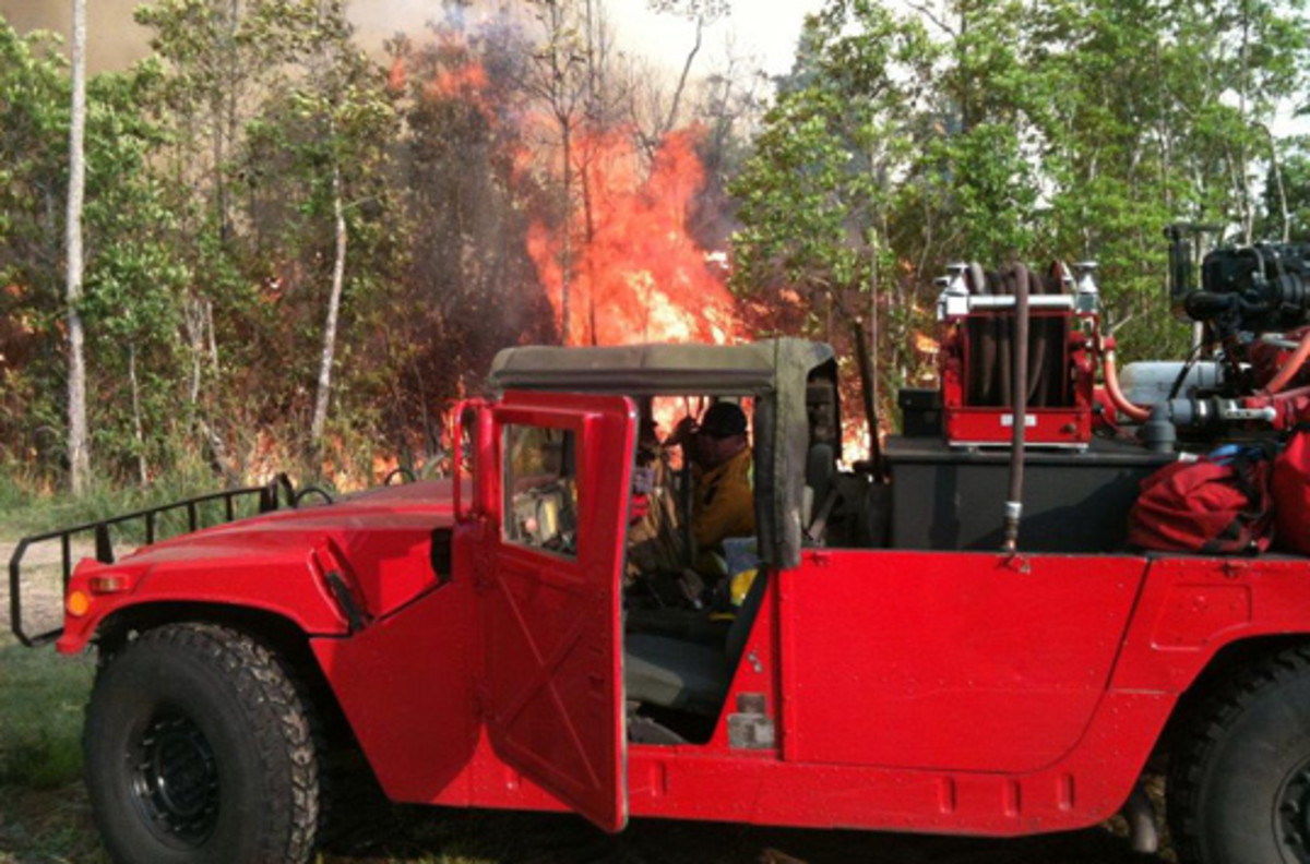 A Putnam County, Florida, firefighter reaches into his vehicle's cab in 2011. The vehicle is a Humvee converted to a brush fire truck. The vehicle was turned in to DLA Disposition Services by the Tennessee Army National Guard and then issued to firefighters in Florida. Photo courtesy Putnam County Emergency Services Department.