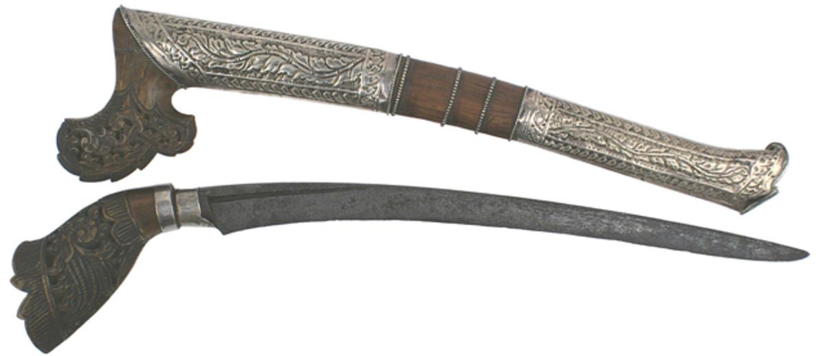 Menangkabau knife of Sumatra featuring intricately carved rhino horn, curved meteorite blade, circa late 19th century.