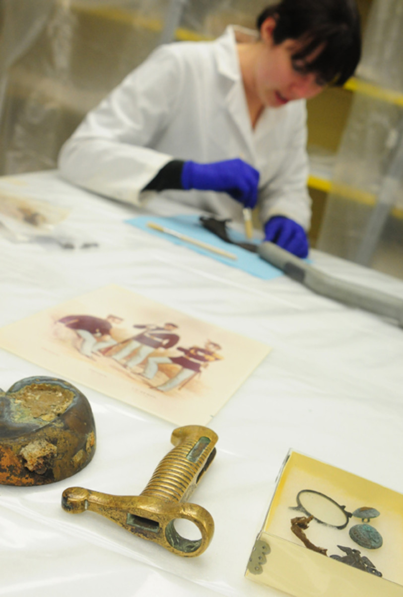 Kate Morrand, archaeological conservator for the Archaeology & Conservation Laboratory at Naval History and Heritage Command, cleans artifacts recovered from the wreck of USS Huron, which sank in a storm off the coast of Nags Head, N.C. in 1877. Ninety-eight men died when Huron sank. The artifacts were removed from the wreck site without permission in the 1960s, and require considerable conservation treatment to stabilize them. (U.S. Navy photo by Mass Communication Specialist 2nd Class Gina K. Morrissette/Released)