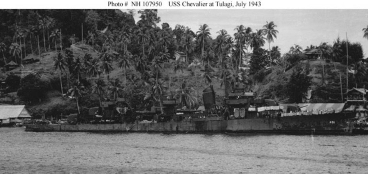(DD-451) Moored to the Government Wharf, Tulagi, Solomon Islands, 6 July 1943. Her bow was damaged while rescuing the crew of the sinking USS Strong (DD-467) during the 5 July 1943 Battle of Kula Gulf, and her 5/58 gun mount # 3 shows the effects of a hang-fire, explosion and fire immediately after that rescue was completed. Courtesy of Rick E. Davis, 2012. This is a cleaned version of National Archives' Photo # 80-G-259220. Official U.S. Navy Photograph, from the collections of the Naval History and Heritage Command.