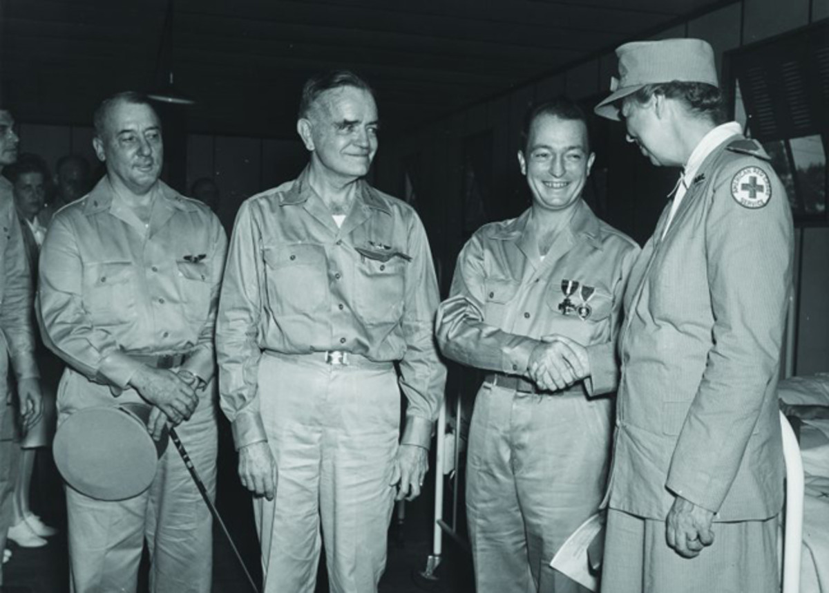 Wearing the Navy Cross and a Purple Heart with Gold Star that Eleanor Roosevelt has just pinned to his newly issued khaki uniform, Hugh Miller shakes hands with the First Lady as Admiral William Halsey (to Hugh's immediate right) looks on. The ceremony—held at the naval hospital in Nouméa, New Caledonia, on September 15, 1943—was conducted at the foot of the bed occupied by Electrician's Mate 2nd Class Willard G. Langley, the sole known survivor of Strong's forward engine room. (National Archives. Courtesy Mr. Stephen Harding)