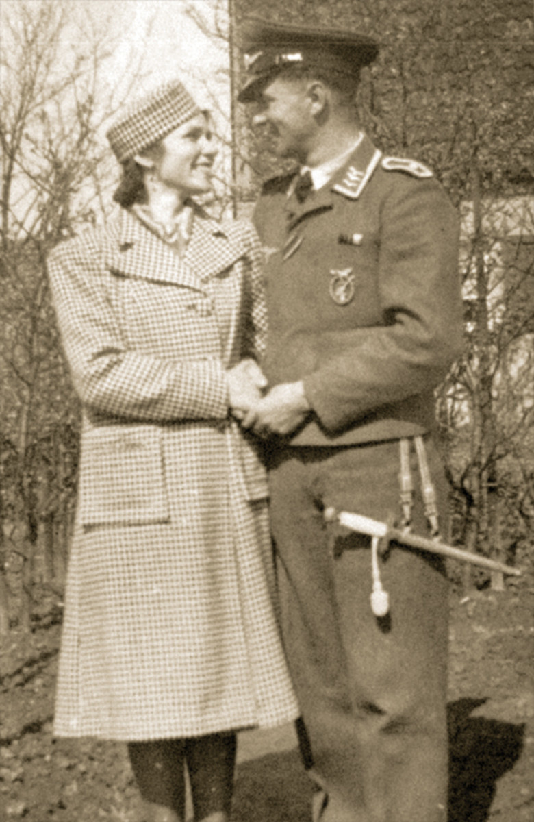 On the arm of his fashionably dressed wife, this flak officer is formally attired with dagger and awards, displaying a flak badge on the left breast of his jacket.
