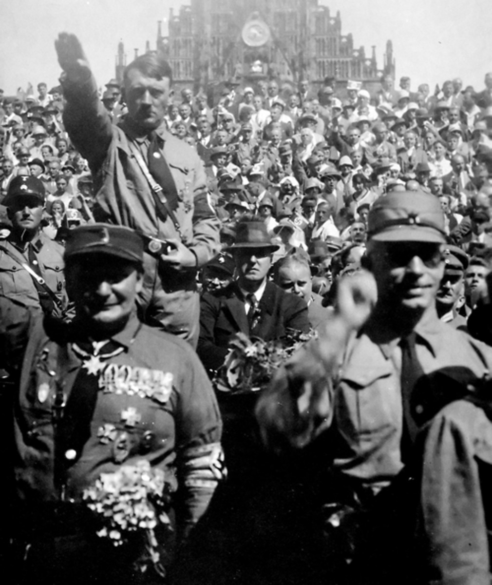 Adolf Hitler raises the Nazi salute behind Herman Goering (left) at an early Third Reich rally.