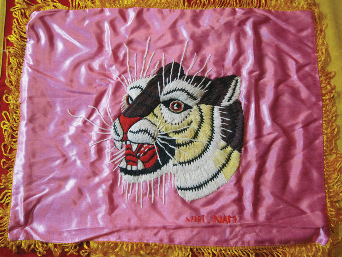 "Wall hangings featuring finely detailed, snarling tigers were popular souvenirs during the Vietnam War. Entirely hand-sewn, these almost always had the word ""Viet-Nam"" on the obverse."
