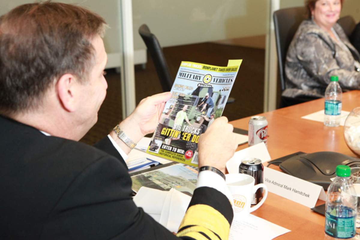 Vice Admiral Mark Harnitchek looked over the current issue of Military Vehicles Magazine while discussing the disposition of HMMWV surplus sales during a meeting with IronPlanet executives.
