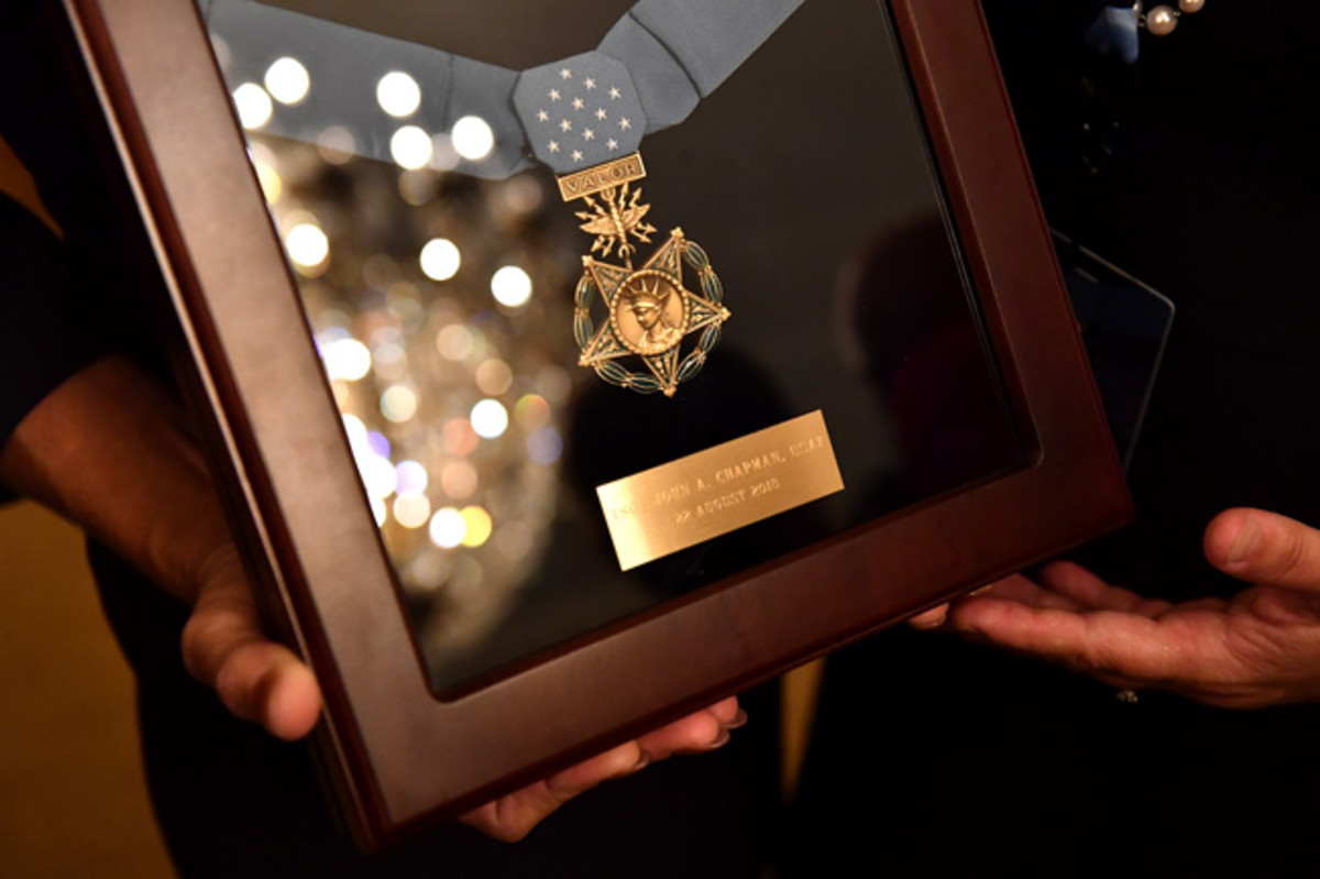 Valerie Nessel, the spouse of U.S. Air Force Tech. Sgt. John Chapman, holds up the Medal of Honor after receiving it from President Donald J. Trump during a ceremony at the White House in Washington, D.C., Aug. 22, 2018. Sergeant Chapman was posthumously awarded the Medal of Honor for actions on Takur Ghar mountain in Afghanistan on March 4, 2002. His elite special operations team was ambushed by the enemy and came under heavy fire from multiple directions. Chapman immediately charged an enemy bunker through thigh-deep snow and killed all enemy occupants. Courageously moving from cover to assault a second machine gun bunker, he was injured by enemy fire. Despite severe wounds, he fought relentlessly, sustaining a violent engagement with multiple enemy personnel before making the ultimate sacrifice. With his last actions he saved the lives of his teammates. (U.S. Air Force photo by Staff Sgt. Rusty Frank)