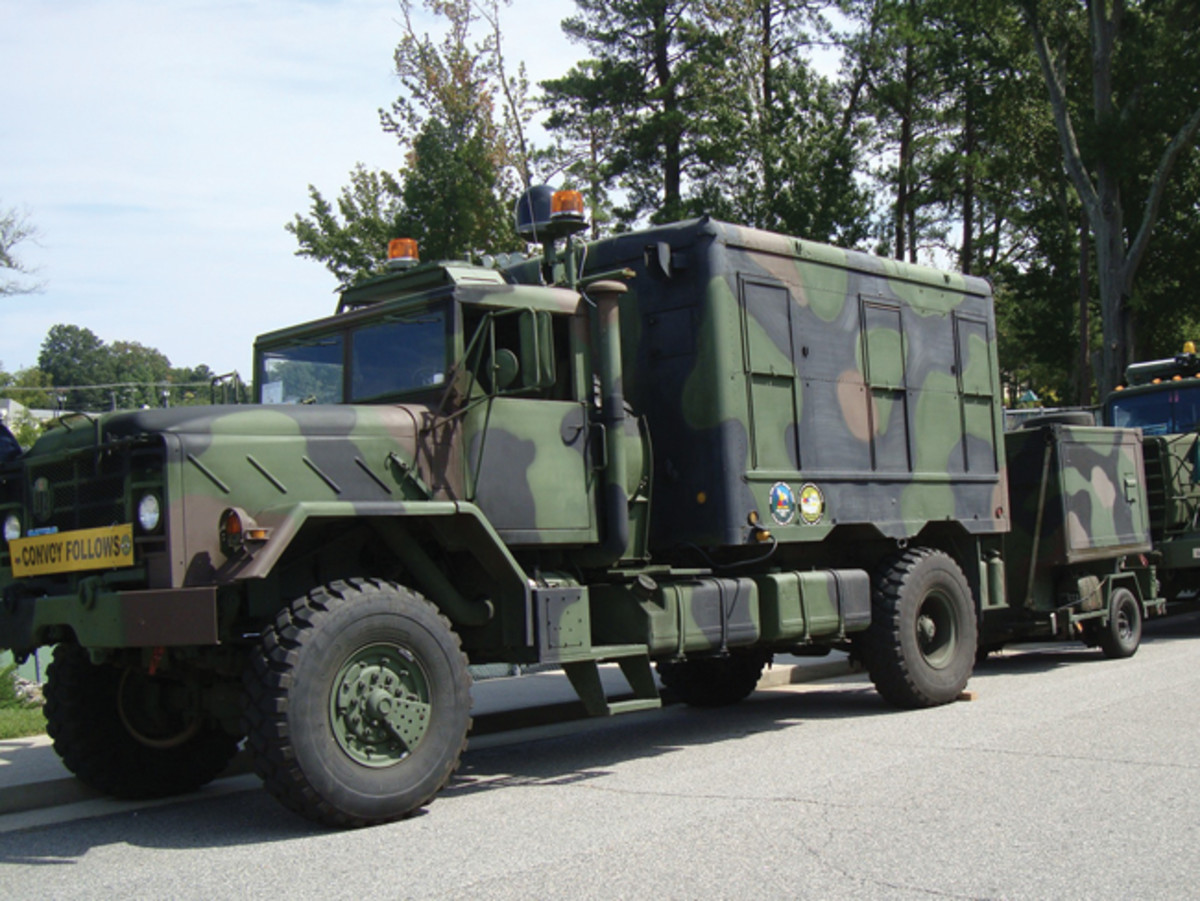 Brad Nelson's M925A2 is modified with M109A3 box converted to living quarters, axle removed and replaced, spare fuel tank and storage, auxiliary generator, air bags on rear axle, roof air conditioning and satellite dome. His S250 trailer is converted to dog tag making facility. Brad has more than 50,000 miles on this combo during the past 6 years.