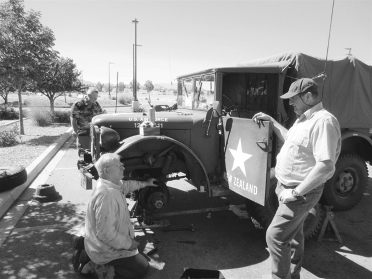 (Left, rear) Peter Yates overseeing Gunnar's work. In the foreground, Ken Field is on his knees deep in discussion with Mike O'Sullivan concerning the merits of various vehicle braking systems. Mark Sigrist