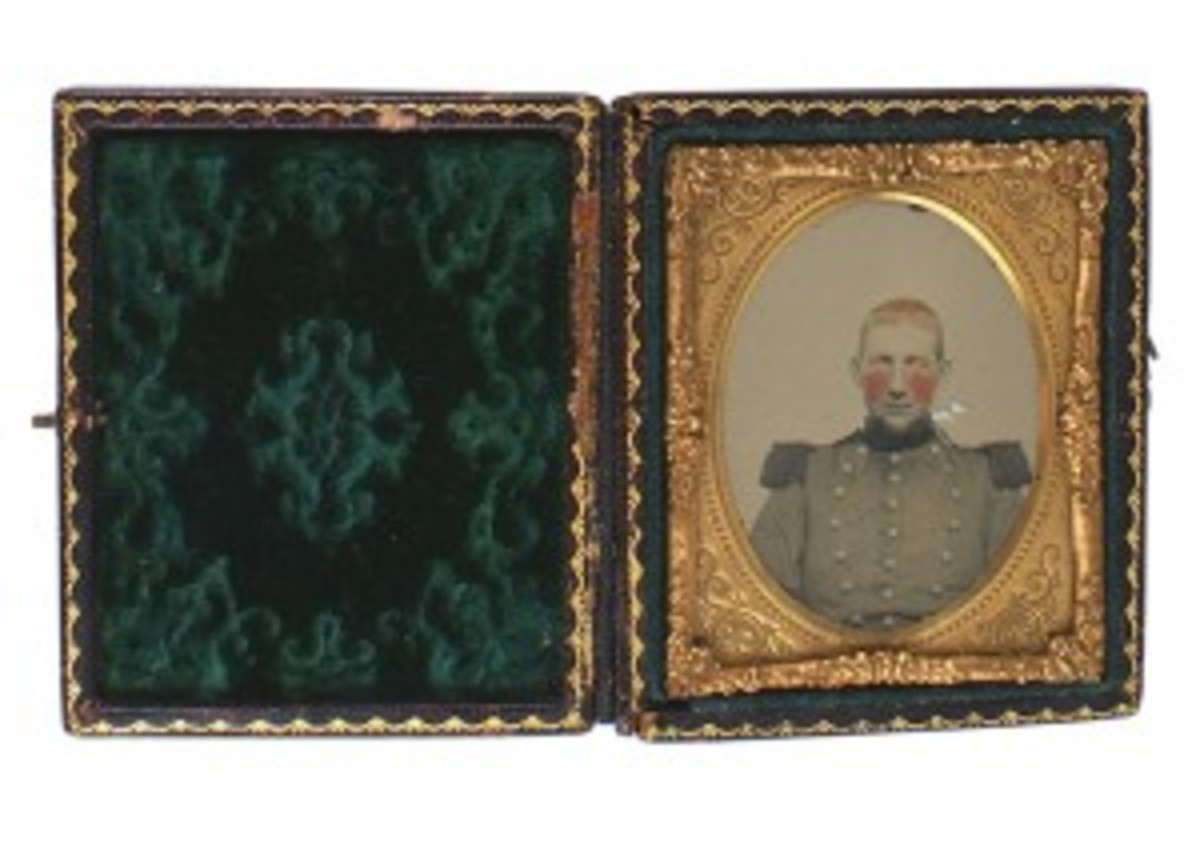 An ambrotype portrait of a red-cheeked Confederate militiaman, very young, dressed in a tunic, in a floral decorated gilt frame and with case ($488).