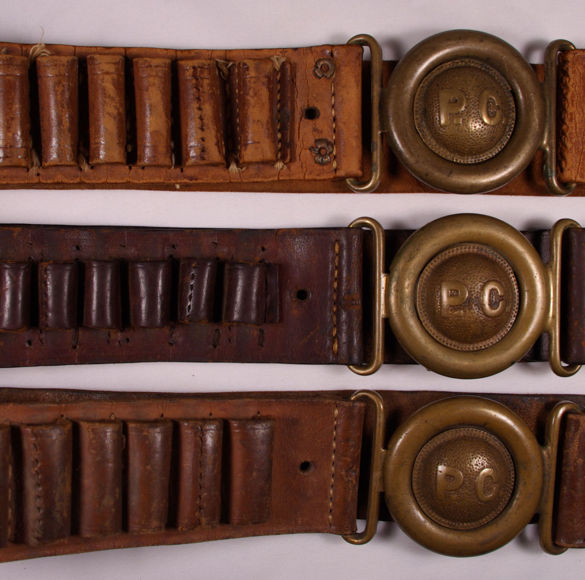 This close-up photo shows stitching holes on the belts that were converted fromshot shells to various rifle or pistol cartridges or combinations.