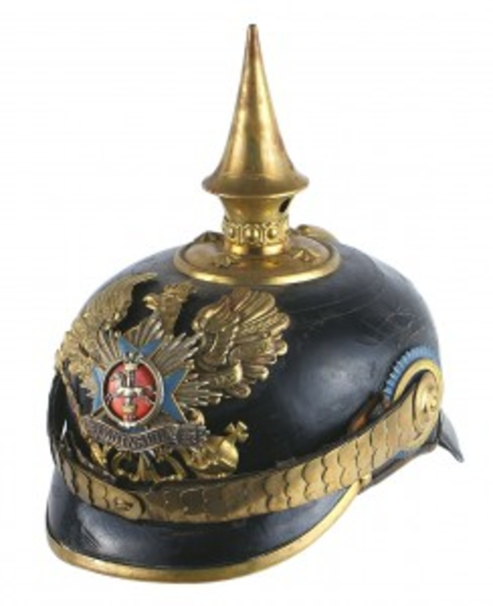 A Prussian officer's helmet – Brunswick 92nd Infantry Regiment, 3rd Battalion – with a solid black leather body, gaveled for $5,400. The rare piece of headgear had an elaborate tiered front plate having an age toned silver oak leaf decorated 'Peninsula' banner affixed to a blue enameled cross, with a detailed galloping horse and crowned pillar, all applied to a convex silver starburst.