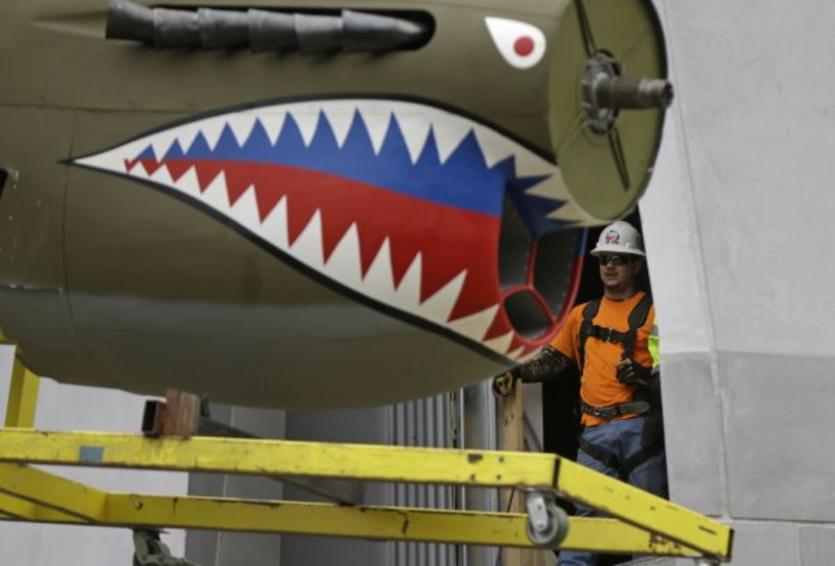A restored P-40 Curtiss Warhawk fighter plane, one of only 32 known remaining in the world, is hoisted by crane to the second floor for permanent display at the National World War II Museum in New Orleans, Feb. 3, 2014.