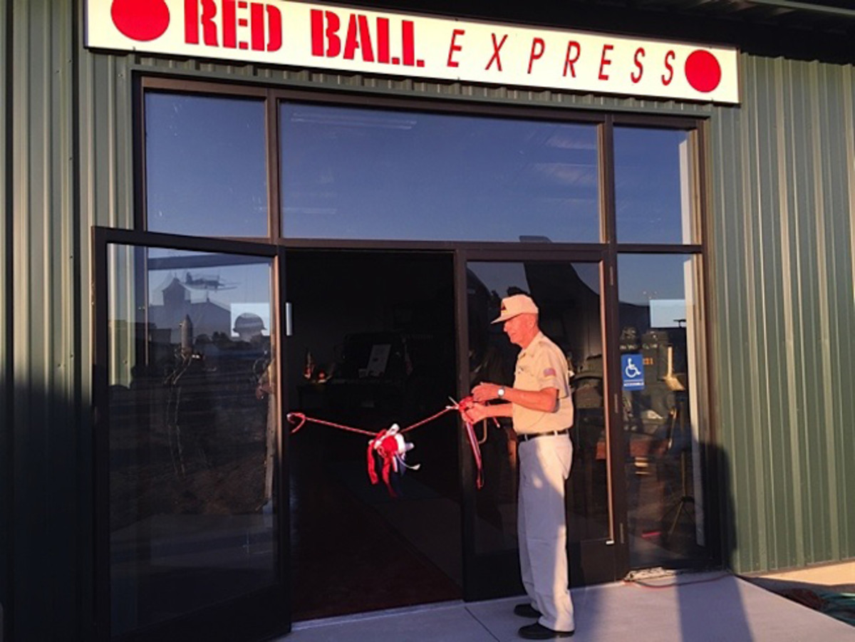 Herman cutting the RED RIBBON to the Red Ball Express Display