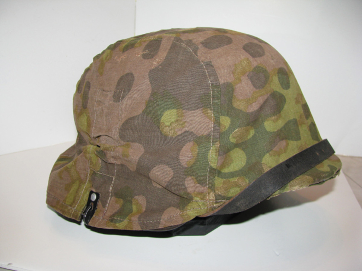 Waffen SS troops often utilized camouflage helmet covers in the field. Later versions of the covers incorporated loops for bush and branches.Mark Pulaski Collection