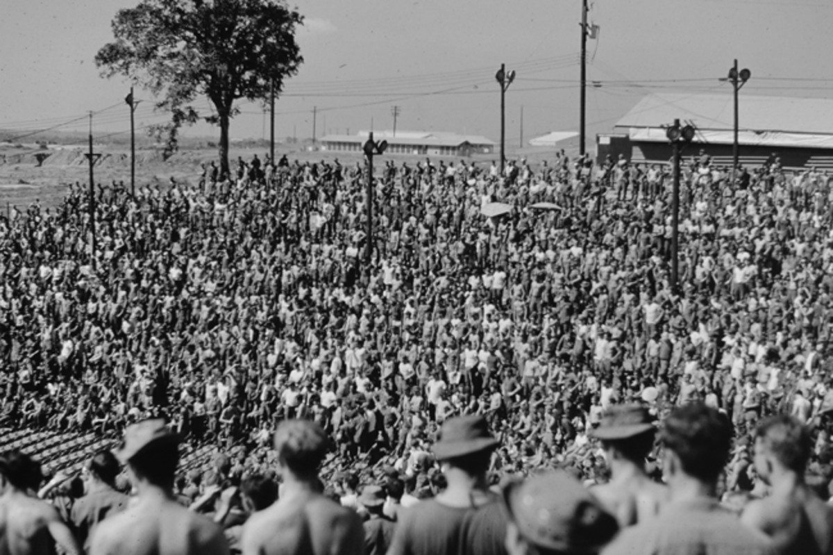 Amphitheater at Long Binh, VietNam Christmas time 1969 crowd of American soldiers awaiting arrival of Bob Hope USO show. Note the empty chairs down front for the just-arriving wounded GIs from the 93rd Evac Hospital.
