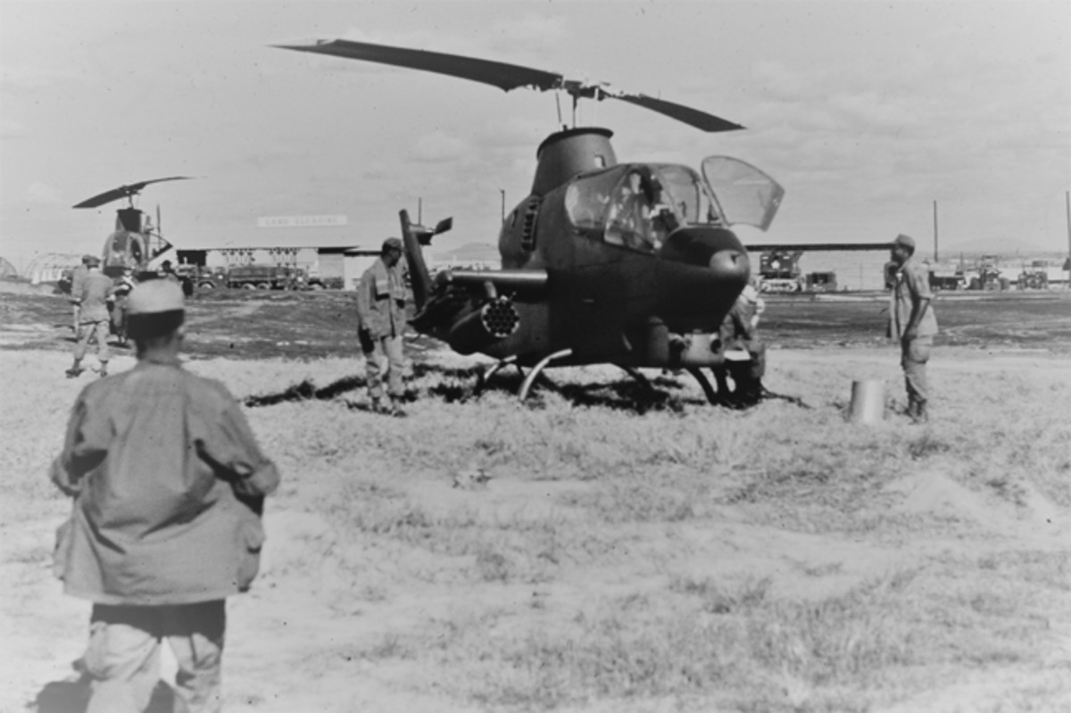 Christmas 1969, Long Binh, Viet Nam. A pair of Cobra gunships photographed on the ground prior to the Bob Hope USO show. During the show, they flew air cover around the area perimeter. A combat engineer land clearing unit provided the LZ.