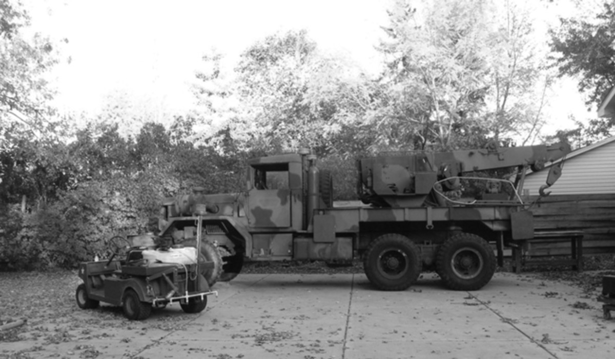 """A rear view of """"Little Cousin"""" showing the hoist boom folded off to the side and secured by its lifting hook. The large silver hoop just to the rear of the operator's station on the M816 is a handrail fabricated for the stairs that are laying on the deck. The stairs are used when the M816 is taken to public events."""