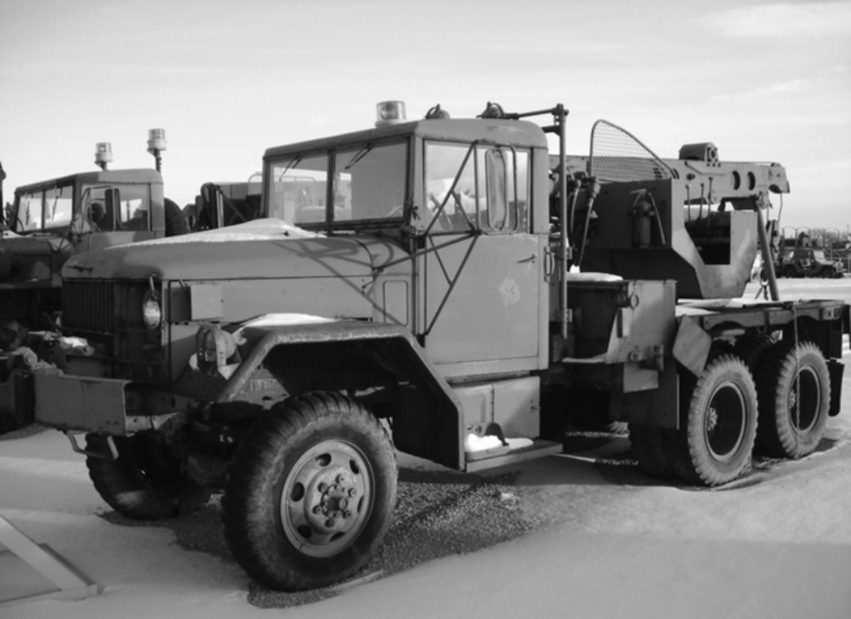 An M108 2-1/2-ton Material Handling Crane Truck parked in the display lot of the Fort Snelling Military Museum. Note the lack of a rear drag winch on the flat rear deck and the stake pockets along the side, for use in installing bows and a tarp for camouflage purposes. Photo courtesy FSMM