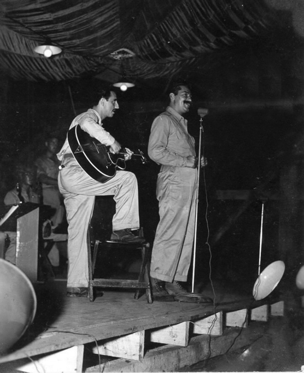 Jerry Colonna of the Bob Hope USO tour performing for members of 3rd Attack Group at Port Moresby, New Guinea.