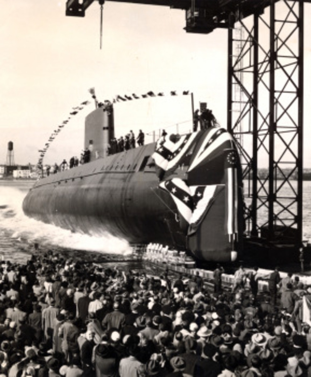 In this file photo taken Jan. 21, 1954, the nuclear-powered submarine USS Nautilus (SSN 571) slips into the Thames River at Groton, Conn., during her christening. Nautilus plankowner Henry Nardone Sr. is on the boat, foot propped on a cleat. (U.S. Navy photo/Released)