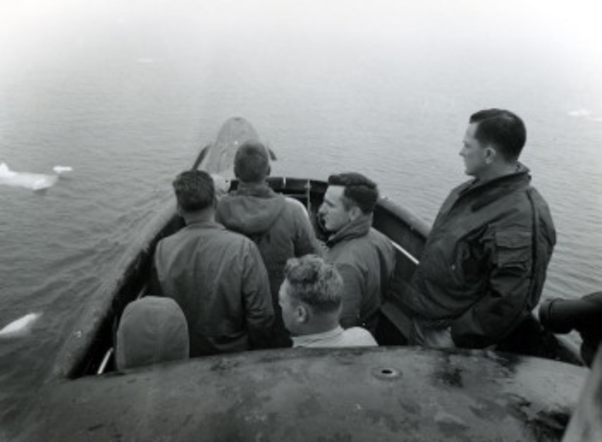 Commander William R. Anderson, USN, Commanding Officer of USS Nautilus (SSN-571), far right, on the bridge during a period of low visibility as the submarine prepares to pass under the North Pole, August 1958. National Archives photograph, USN 1037145