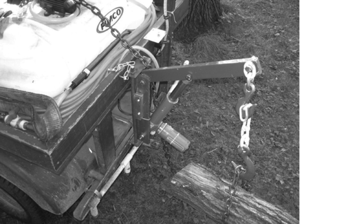 The boom is locked in its working position and used to lift one end of a 30-foot section of a felled tree. The linear actuator that provides the lifting force is positioned just above the rear bumper. The spray bar that is attached to the rear bumper is fed from the tank on the rear deck, as is the wand. Both are used in weed control around the property.