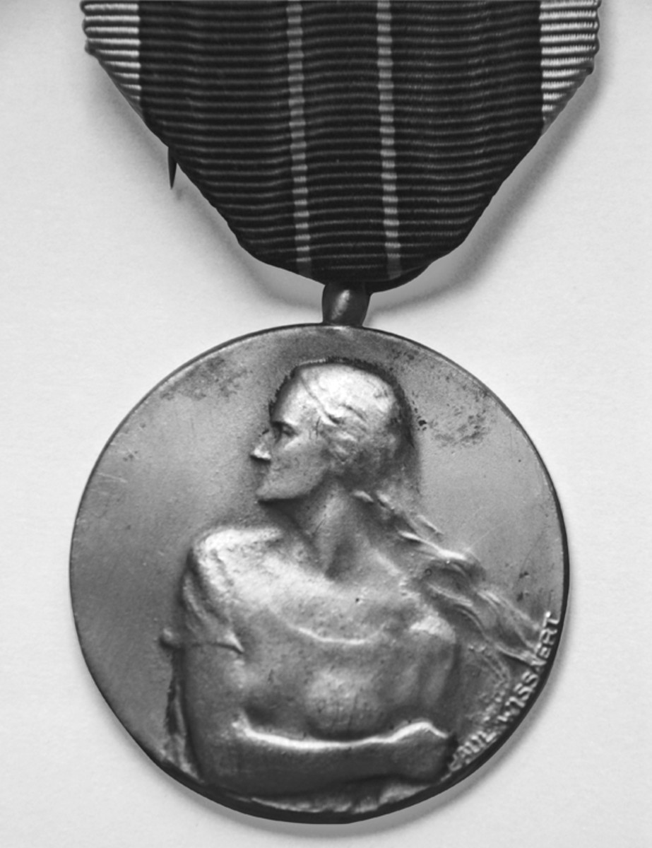 Obverse of the Belgian Resistance Medal with designer's name, Paul Wissanert, on the edge to the right by the woman's fist.
