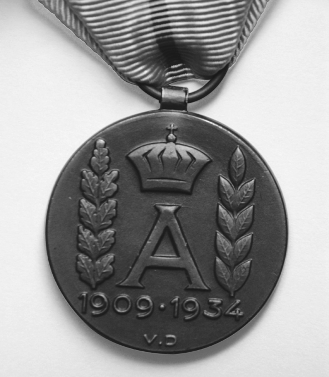 Reverse of the Commemorative Medal showing the designer's initials 'VD' (Victor Demanet) just below the letter 'A'.