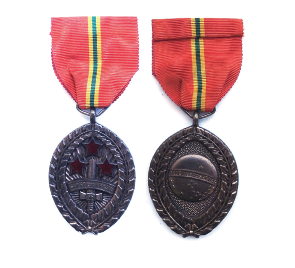 Blood of Brazil Medal features Brazilwood branches along the edge, symbolizing the tree for which the nation of Brazil was named. The three red enameled stars symbolize the mortal wounds suffered by Gen. Antônio de Sampaio during the Triple Alliance War.