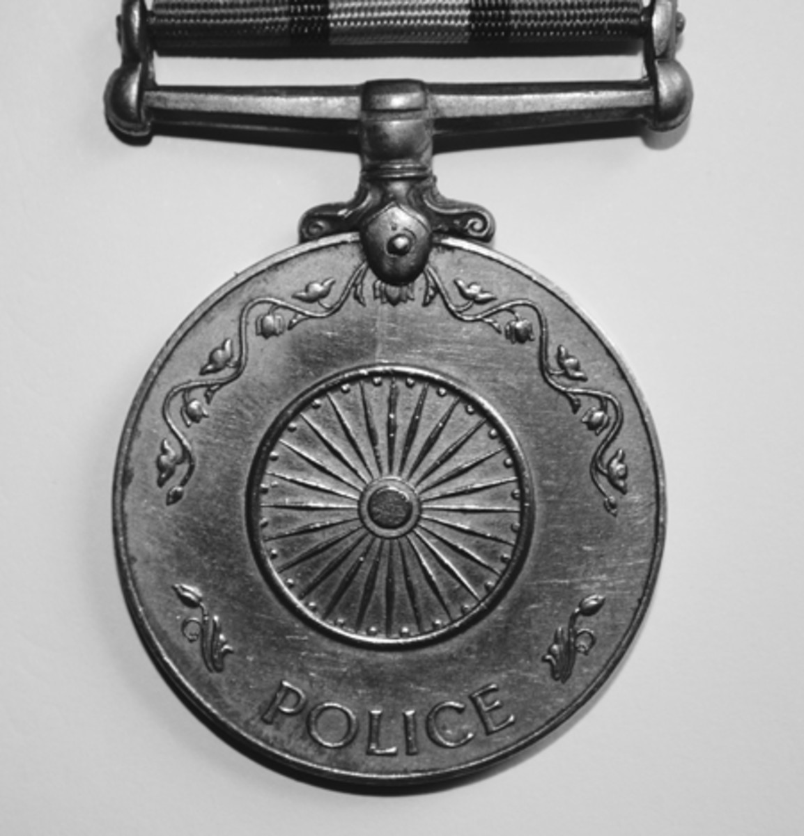 Reverse of Police Independence Medal with chakra symbol.
