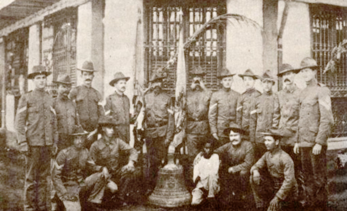 Extant photograph of some American survivors with their bell of Balangiga. This photo was taken in Calbayog, Samar, sometime in April 1902.