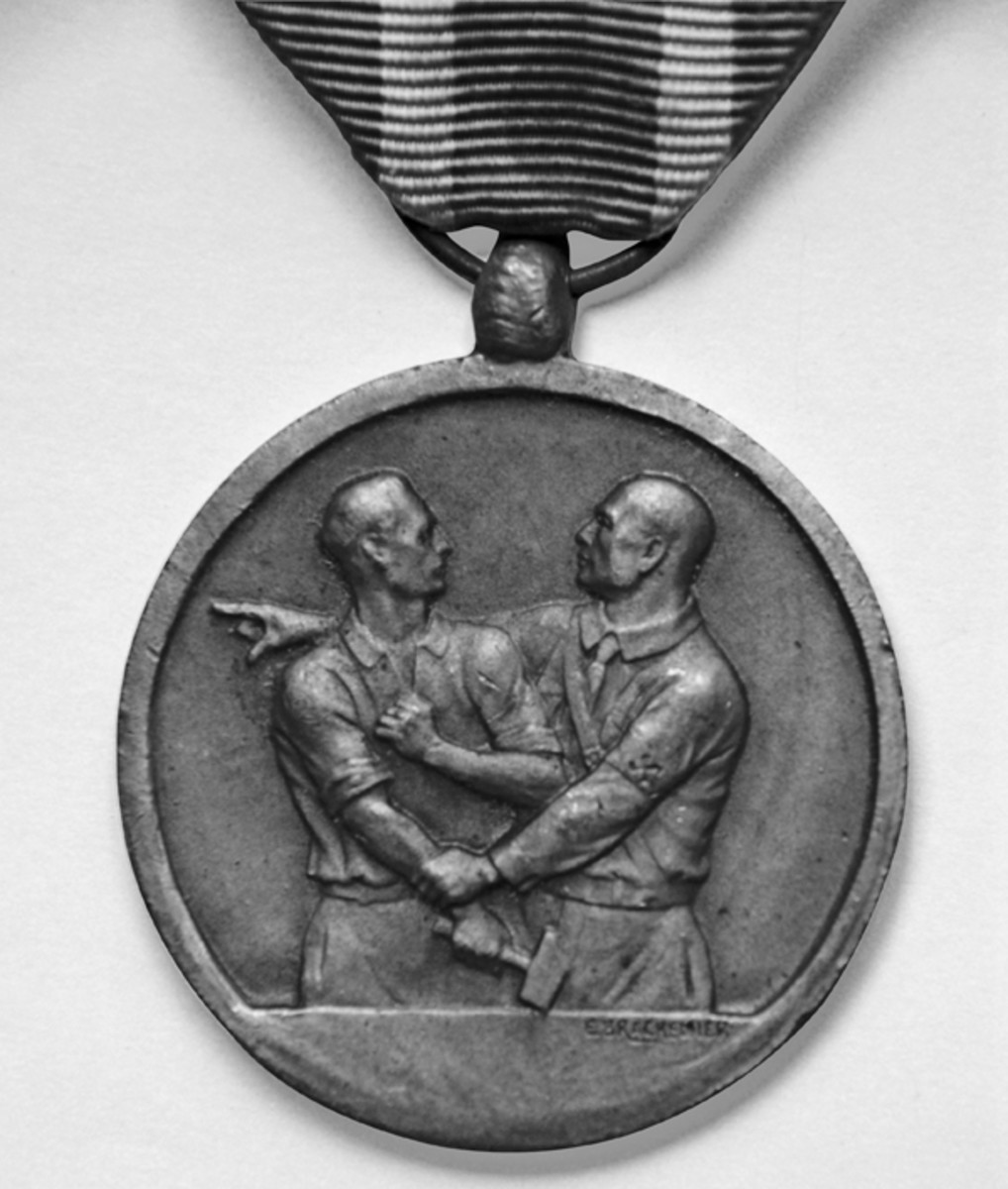 Obverse of the unofficial Belgian Medal for those deported, showing the oppression of the time. The designer's name, E. Brackenier, is visible below the waist of the man on the right.