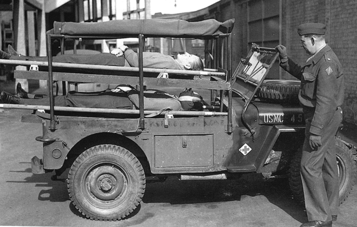 Holden modifications to jeeps included a pipe and angle-iron framework to support a canvas enclosure and provide racks for two stretchers, as well as seating in the rear for two ambulatory patients. Access for the latter made a bit easier by the addition of a small door on the left side of the rear body panel. A compartment for medical supplies was built into the right body side and extended into the area which would normally be occupied by a jeep's front seat passenger. The windshield frame was bent vertical to accommodate the new structure, and the spare wheel mounted on the hood.